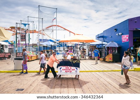 LOS ANGELES, CA - SEP 12, 2015: People walking by Santa Monica end of famous Route 66 in Santa Monica Pier - stock photo
