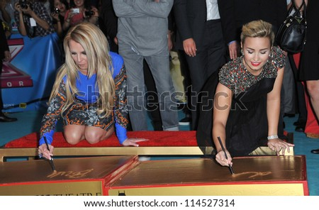 """LOS ANGELES, CA - SEPTEMBER 11, 2012: Britney Spears & Demi Lovato (right) at the season two premiere of """"X Factor USA"""". They had their handprints set in cement at Grauman's Chinese Theatre - stock photo"""