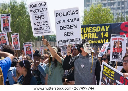 Los Angeles, CA, USA - April 14, 2015:  Man wearing mask holding a sign and blowing a whistle during Stop Murder by Police. Protest against the brutalization and murdering of black and latino people.
