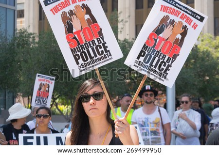 Los Angeles, CA, USA - April 14, 2015:  Woman holding two signs during Stop Murder by Police. Protest against the brutalization and murdering of black and latino people by police.
