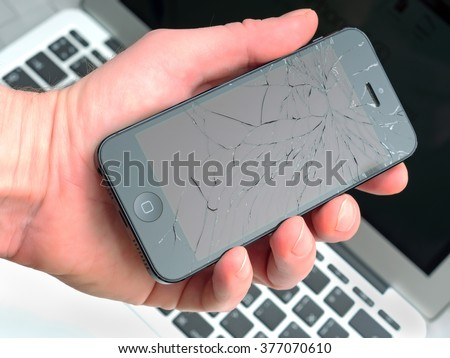 Los Angeles, CA, USA - December 07, 2015: Man holds in his hand broken Apple iPhone with cracked screen - stock photo