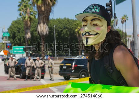 Los Angeles, CA, USA - May 02, 2015: Anonymous with mascara with police in the background during march against the death of Freddie Gray, a man of Baltimore who was seriously injured in police custody - stock photo