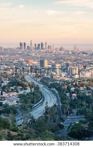 LOS ANGELES, CALIFORNIA - FEB 13: Sunrise towards a smog ridden Los Angeles downtown from Hollywood Hills on February 13, 2016.  LA is well known for its Hollywood film district. - stock photo
