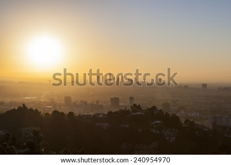 LOS ANGELES, CALIFORNIA - JANUARY 1, 2015:  Smoggy orange new years day sunrise above Hollywood and Downtown Los Angeles.   - stock photo