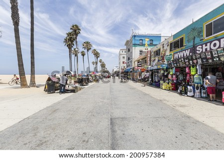LOS ANGELES, CALIFORNIA - June 20, 2014:  Shops and tourists on the famously funky Venice Beach board walk in Los Angeles.  - stock photo