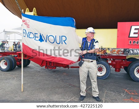 LOS ANGELES/CALIFORNIA - MAY 18, 2016: Crew member of the transport team of ET-94 holds up flag of Endeavor along side massive fuel tank destined for the science center in Los Angeles, California USA - stock photo
