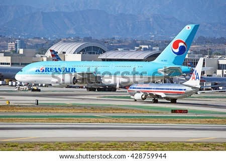 LOS ANGELES/CALIFORNIA - MAY 22, 2016: Korean Air Airbus A380-861 and American Airlines traverse the tarmac at Los Angeles International Airport, Los Angeles, California USA - stock photo