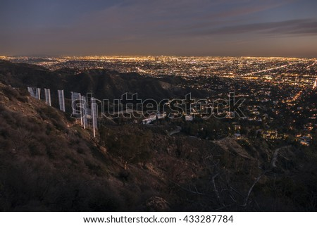 Los Angeles, California, USA - February 4, 2016:  Hollywood sign and downtown Los Angeles hilltop cityscape dusk view.   - stock photo