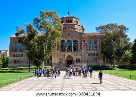 Los Angeles, California, USA - July 9. 2015: A group of people (students and families) get a guided tour of the University of California Los Angeles (UCLA) campus. Powell Library is in the background. - stock photo