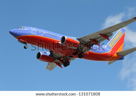 LOS ANGELES, CALIFORNIA, USA - MARCH 8, 2013.   Southwest Airlines Boeing 737-7H4 lands at Los Angeles Airport on March 8, 2013. The plane has a range of 6,340 miles with 177 seats. - stock photo