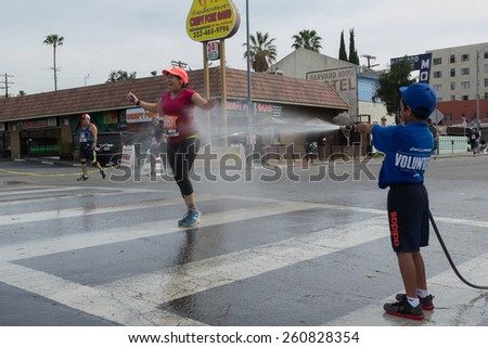 Los Angeles, California, USA - March 15,2015:  Unidentified volunteer boy throwing water in a runner