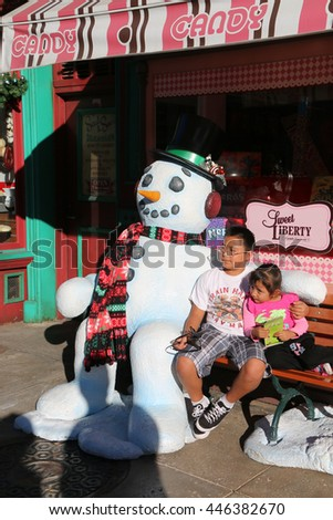 Los Angeles, California, USA - November 22, 2015: Children is taking photos with snowman decorated for Christmas season at Universal Studios Hollywood. - stock photo