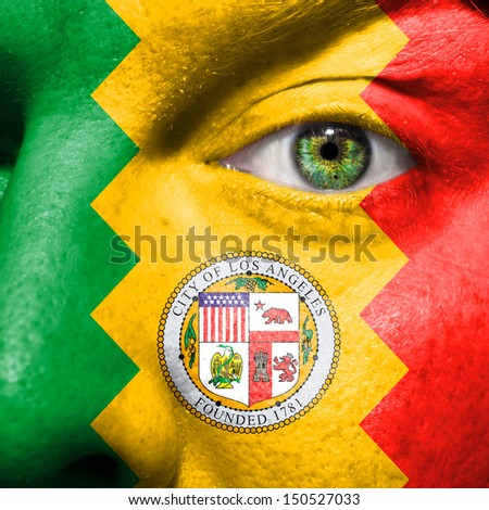 Los Angeles city flag painted on a man's face with a green eye to show Los Angeles support