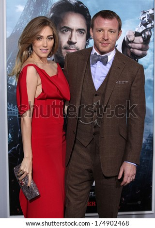 "LOS ANGELES - DEC 06:  GUY RITCHIE & JACQUI AINSLEY arrives to the ""Sherlock Holmes A Game of Shadows"" Los Angeles Premiere  on December 06, 2011 in Westwood, CA                 - stock photo"