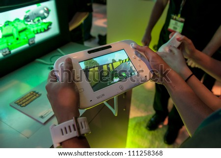 LOS ANGELES - JUNE 8: A journalist playing with a Nintendo WiiU final retail controller during E3 2012, world video games Expo June 8, 2012 in Los Angeles, CA - stock photo