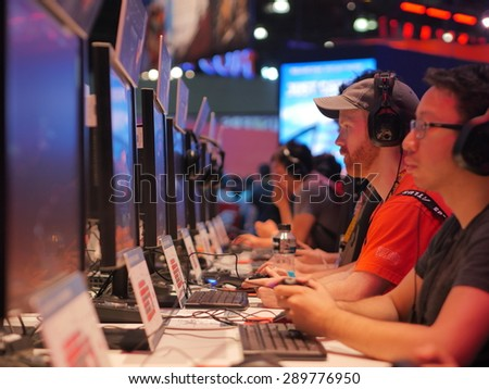 LOS ANGELES - June 17: Gamers playing demo video games at E3 2015 expo. Electronic Entertainment Expo, commonly known as E3, is an annual trade fair for the video game industry - stock photo