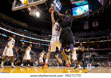 LOS ANGELES - MARCH 12: Arizona Wildcats F Jesse Perry #33 (L) & Washington Huskies F Darnell Gant #44 (R) during the NCAA Pac-10 Tournament championship gameon March 12 2011 at Staples Center. - stock photo