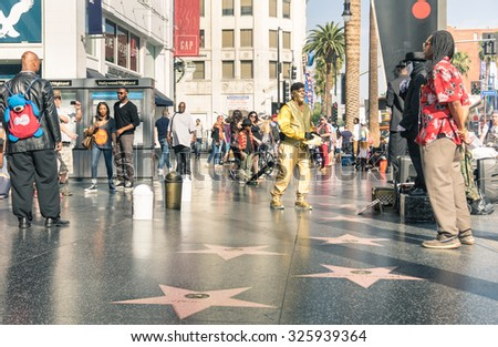 LOS ANGELES - MARCH 21, 2015: street artists and everyday multiracial people around the world famous Walk Of Fame in late afternoon on Hollywood Boulevard in LA California - United States of America - stock photo
