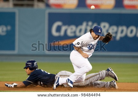 LOS ANGELES - MAY 16: Milwaukee Brewers CF Carlos Gomez #27 steals second past Los Angeles Dodgers 2B Aaron Miles #6 during the MLBL game on May 16 2011 at Dodger Stadium in Los Angeles. - stock photo