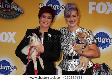 "LOS ANGELES - NOV 22:  Sharon Osbourne, Kelly Osbourne at the FOX's ""Cause for Paws:  All-Star Dog Spectacular"" at the Barker Hanger on November 22, 2014 in Santa Monica, CA - stock photo"