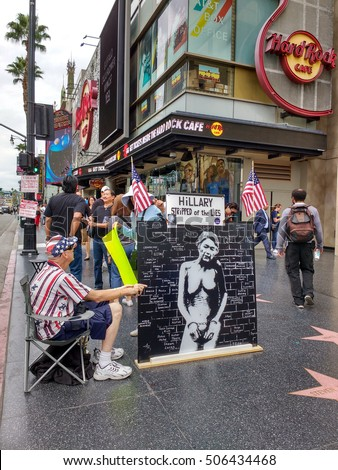 LOS ANGELES, OCT 29TH 2016: A Trump supporter with a painting depicting Hillary Clinton in handcuffs sits on the Hollywood Walk of Fame near the site where Donald Trump's star was vandalized on Oct 26