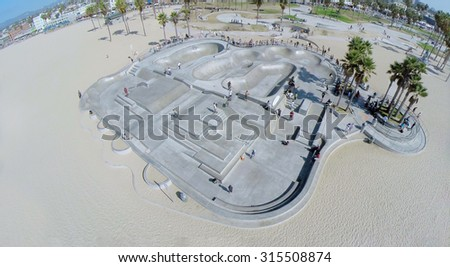 LOS ANGELES - OCT 19, 2014: Venice Beach Skate Park with many young people ride on skateboards at autumn sunny day. Aerial view. Venice Beach is the most popular beaches of LA County. - stock photo