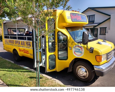 LOS ANGELES, SEP 14TH 2016: Close-up of a yellow Hollywood Starline tour bus with its doors wide open parked in a quiet, idyllic residential street.