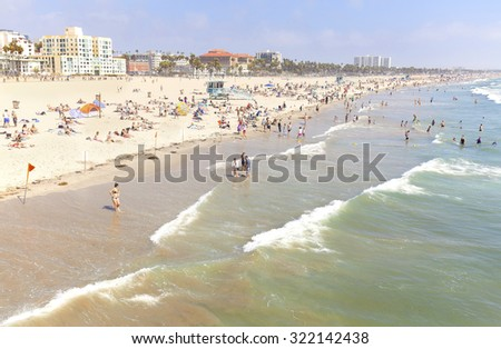 LOS ANGELES, USA - AUGUST 22, 2015: People resting on the Venice Beach during peak season. Venice was an independent city until 1926, when it merged with Los Angeles.  - stock photo