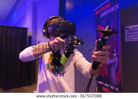 Los Angeles, USA - January 23, 2016: Man tries virtual reality HTC Vive headset during and hand controls VRLA Expo Winter, virtual reality exposition, at the Los Angeles Convention Center. - stock photo