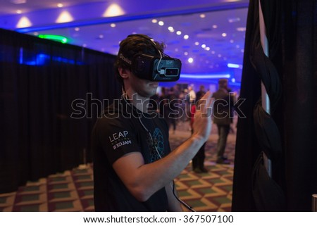 Los Angeles, USA - January 23, 2016: Man tries virtual reality Oculus Rift  headset during VRLA Expo Winter, virtual reality exposition, at the Los Angeles Convention Center. - stock photo