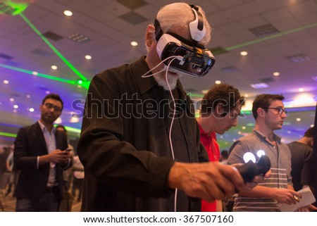 Los Angeles, USA - January 23, 2016: Man tries virtual reality Samsung Gear VR headset and hand controls during VRLA Expo Winter, virtual reality exposition, at the Los Angeles Convention Center. - stock photo