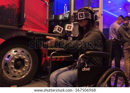 Los Angeles, USA - January 23, 2016: Woman tries Overkills The Walking Dead VR-experience during VRLA Expo Winter, virtual reality exposition, at the Los Angeles Convention Center. - stock photo