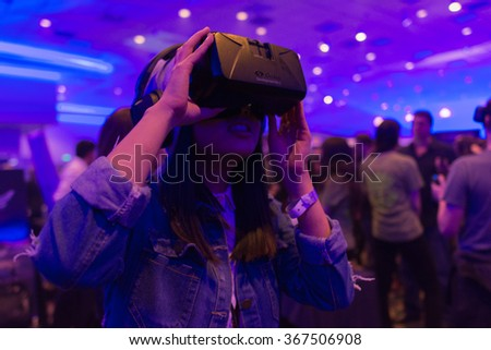 Los Angeles, USA - January 23, 2016: Woman tries virtual reality Samsung Gear VR headset during VRLA Expo Winter, virtual reality exposition, at the Los Angeles Convention Center.