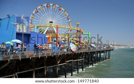 LOS ANGELES, USA - JULY 14, 2013: Ferris Wheel and attractions on Santa Monica Pier on July 14, 2013 in Los Angeles. - stock photo
