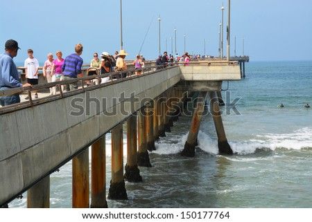 LOS ANGELES, USA - JULY 14, 2013: Fishermen try their luck on the Venice Beach Pier on July 14, 2013 in Los Angeles. - stock photo