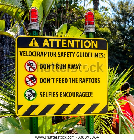 LOS ANGELES, USA - SEP 27, 2015: Attention sign in Jurassic Park area in the Universal Studios Hollywood Park. Jurassic Park is a 1993 American adventure film  by Steven Spielberg - stock photo
