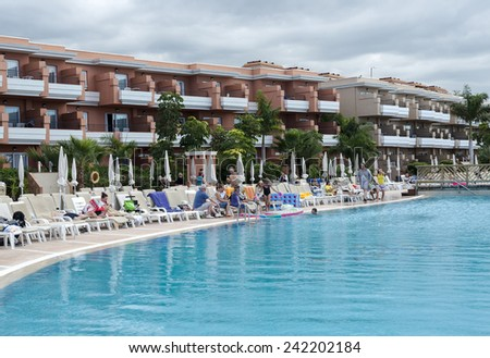 LOS CHRISTIANOS,TENERIFE-NOVEMBER 28, 2014: People enjoy vacation near the swimming pool at resort in Tenerife, on November 28,Tenerife tis one of the popular island of canadian islands.