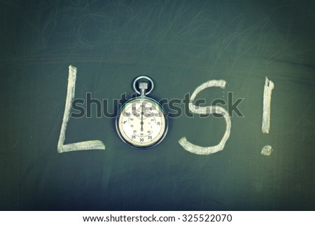 LOS (german word for go) word handwritten on chalkboard with vintage precise stopwatch used instead of O