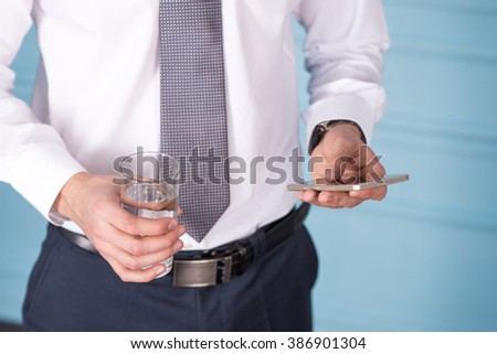 lose-up of a man with a phone and a glass of water in hands - stock photo