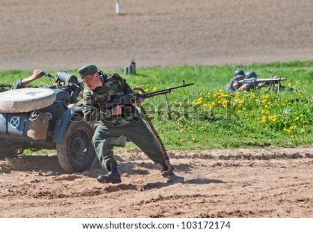 LOSHANY, BELARUS - MAY 9: a military history club member in German WWII uniform dashes to cover during historical reenacting show at Stalin's Line memorial on May 09, 2012 in Loshany, Belarus - stock photo