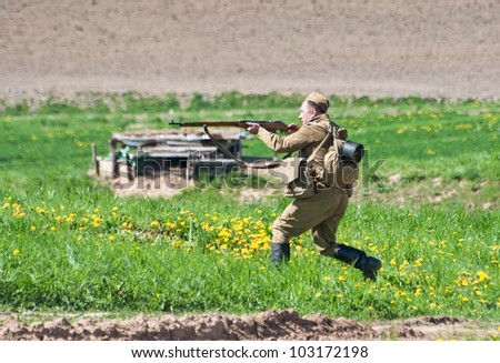 LOSHANY, BELARUS - MAY 9: a military history club member in Soviet WWII uniform aims his rifle during historical reenacting show at Stalin's Line memorial on May 09, 2012 in Loshany, Belarus - stock photo