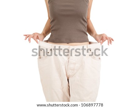 losing weight - anonymous woman showing how much weight she lost, white background - stock photo