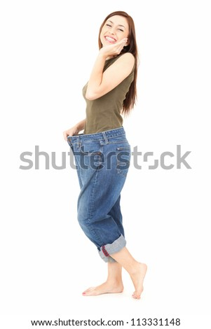 losing weight, young woman showing how much weight she lost, white background - stock photo