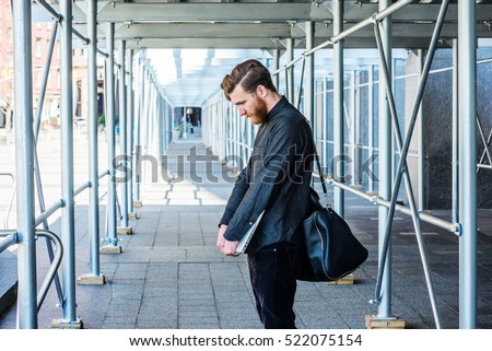 Lost. American student with beard, mustache studies in New York. Business man, shoulder carries bag, holds laptop computer, stands on sidewalk bridge, lowers head, sad. Filtered look with blue tint.