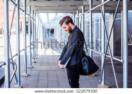 Lost. American student with beard, mustache studies in New York. Business man, shoulder carries bag, holds laptop computer, stands on sidewalk bridge, lowers head, sad. Filtered look with purple tint.