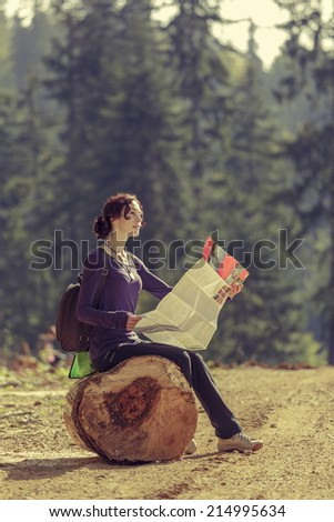 Lost beautiful young woman traveler resting on a stump and reading a travel map during a hike in the mountains. - stock photo