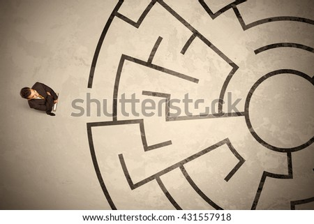 Lost business man looking for a way in circular labyrinth concept - stock photo