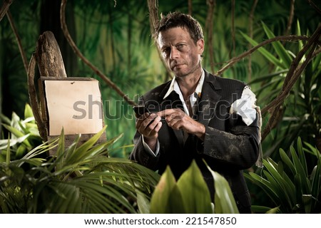 Lost businessman in torn clothing using mobile phone in the jungle. - stock photo