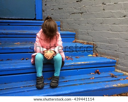 Lost child (girl age 6) cries on steps in a city street alley. - stock photo