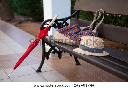 Lost female things on a wooden bench in a summer park - stock photo